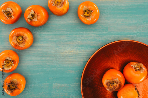 Foto Murales top view of persimmons on red plate and turquoise table