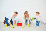 A happy family is washing the floor against a white wall. - 192976458