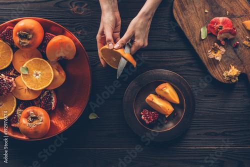 cropped image of woman peeling orange