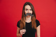 Portrait of a cheerful girl grimacing with fake moustaches
