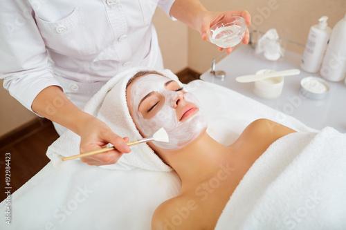 Kobieta w masce na twarzy w spa salon kosmetyczny.