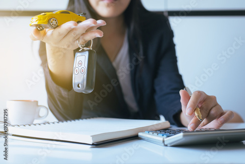 Car key on hand for vehicle sales agreement,Car finance and loan concept