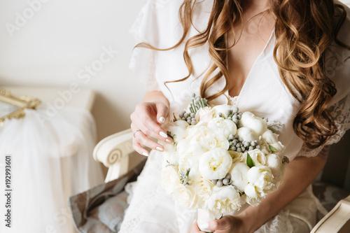 Bride in a white wedding dress holding tender bouquet. Bridal boudoir.