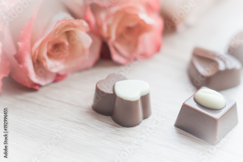 chocolate sweets and pale roses on wooden table, toned