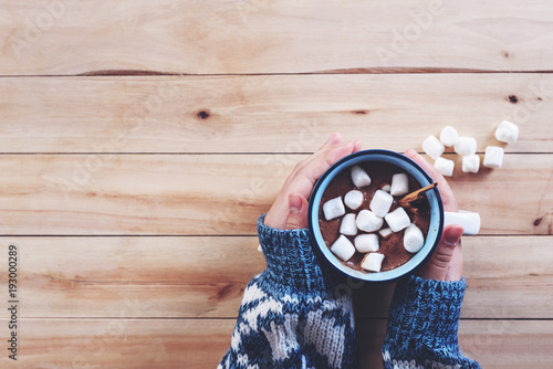 Fotobehang Chocolade a cup of hot chocolate with marshmallow in women hands