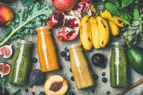 Flat-lay of colorful smoothies in bottles with fresh tropical fruit and vegetables on concrete background, top view. Healthy, clean eating, vegan, vegetarian, detox, dieting breakfast food concept - 193003487
