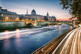 Seine river in Paris, France at sunset. Traffic on water and on the road.