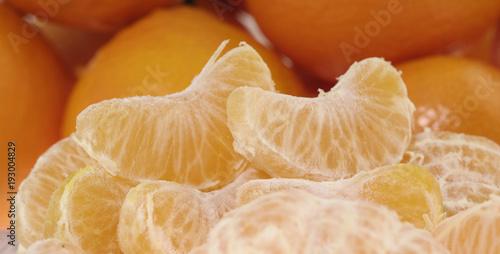 Whole orange fruits and peeled segments