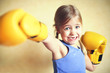 Quadro Little girl with yellow boxing gloves over yellow wall background. Girl power concept. Funny little kid portrait.