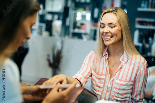 Gorgeous young woman getting her nails done by a manicurist - 193010633