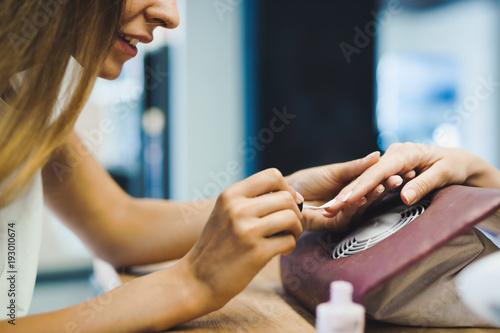 Foto op Plexiglas Manicure Portrait of woman doing nail polish in beauty salon