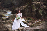 The bride sits on stones high in the mountains by the river.  Wedding day. - 193013259