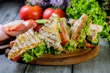 Panini sandwich with ham, tomato and lettuce.