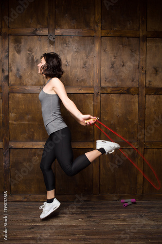 Side view image of girl jumping on rope. Sport concept.