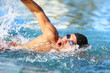 Man swimmer swimming crawl in blue ocean open water. Portrait of an athletic young male triathlete swimming crawl wearing cap and swimming goggles. Triathlete training for triathlon.