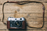 Old vintage film photo camera with brown leather strap on grunge wooden table. Photographe concept background - 193023028