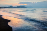 Picturesque seascape on beauty seacost. Sandy beach and blurred waves glowing by sunrice light. Vacations travel concept - 193023242
