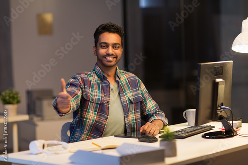 creative man showing thumbs up at night office