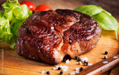 Papiers peints Steakhouse grilled beef steak with herbs on wooden background