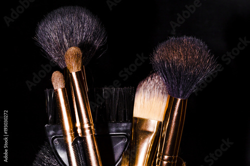 a set of brushes after make-up in a glass, on a black background