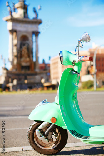 Fotobehang Barcelona Vintage bright green scooter parked on the street of Barcelona on a sunny day
