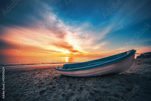Tuinposter Zee zonsondergang Boat on the beach and beautiful sunrise