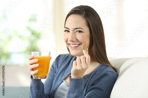 Girl holding an orange juice and a pill looking at you