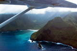 Aerial view of the sea cliffs of Molokai, Hawaii, the highest in the world, with the wing of a small prop plane - 193075290