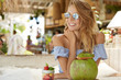 Fashionable young female with bare shoulders, wears stylish summer blouse and trendy shades, admires something with happy expression, drinks coconut cocktail, spends spare time in exotic cafe