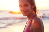 Pretty cheerful fitness female rests after run on coastline, admires beautiful sunrise and seascape, has much energy. Young active athlete takes break after outdoor workout during sunny summer weather - 193082617