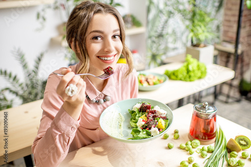 Foto Murales Young woman eating healthy food sitting in the beautiful interior with green flowers on the background