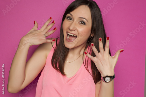 Poster Manicure Young smiling woman showing her nails on pink background