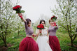 Fabulous bride and her bridesmaids holding bouquets and feeling elated in the garden on wedding day.