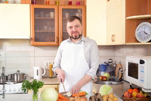 Man in the kitchen is preparing a salad of fresh vegetables. Vegetarian menu. - 193097249