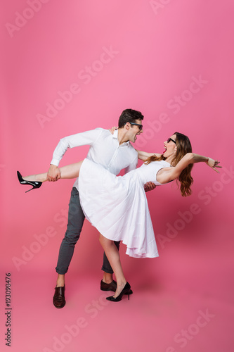 Full-length image of beautiful loving couple in sunglasses dancing together and enjoying party, isolated over pink background