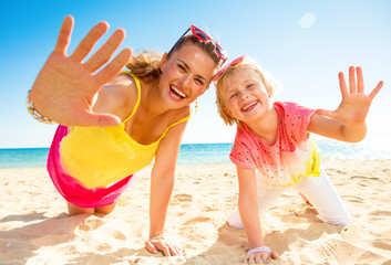 smiling modern mother and child on seashore showing palms