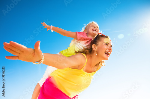 happy trendy mother and child on seashore having fun time