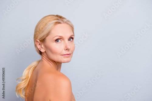 Leinwanddruck Bild Portrait with copy space, empty place for product, advertisement, concept, charming, pretty, attractive woman with perfect skin after cream, massage, balm, mask, lotion, isolated on grey background
