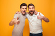 Portrait of a two happy young men showing thumbs up