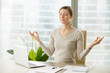 Leinwanddruck Bild - Relaxed woman meditating at workplace, practicing eastern spiritual practices for stress relief and mental health while sitting at desk in front of laptop. Short break in work for strength recovery