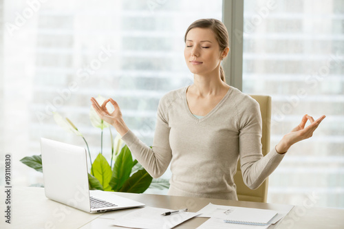 Leinwanddruck Bild Relaxed woman meditating at workplace, practicing eastern spiritual practices for stress relief and mental health while sitting at desk in front of laptop. Short break in work for strength recovery