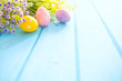 Quadro Beautiful Easter eggs and flowers on blue wooden background.