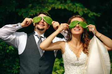 Bride and groom hold green leaves before their eyes standing in the garden