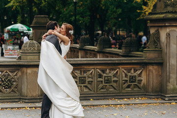 Bride and groom hug each other tender and kiss standing in the Central Park, New York