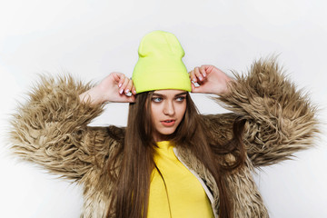 Girl in yellow hat and fur jacket looks modern posing in a white studio