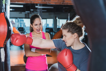 overweight woman having boxing training while trainer shouting her