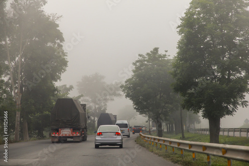 Blurred hard foggy road with detail of car light, travel in winter, car or dangerous winter transportation concept.