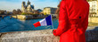 Seen from behind traveller woman with French flag in Paris
