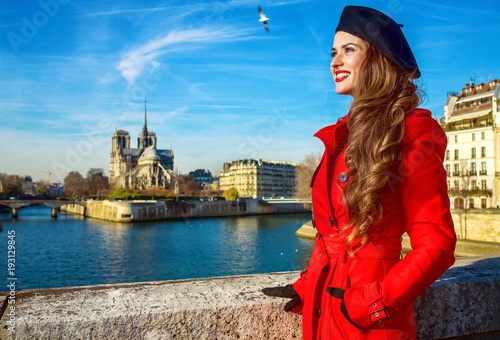 tourist woman in red trench coat in Paris, France looking aside - 193129845