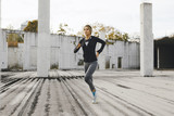 Young fit woman running in the industrial urban zone, side view of fitness girl running - 193133261